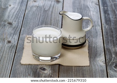 Fresh glass of milk and pourer on rustic wood  - stock photo