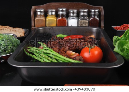 fresh glazed baked big beef meat rib chunk under sweet sauce with lettuce broccoli tomatoes hot chili pepper pink peppercorn different spices on black wooden table - stock photo