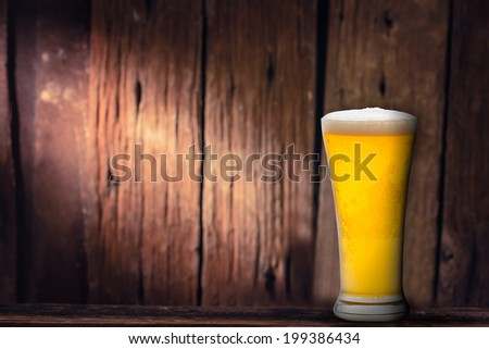 Fresh gold cold and delicious beer in  glass on wooden background