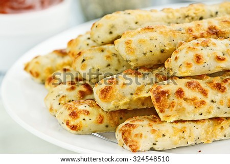Fresh golden, cheesy breadsticks with marinara sauce and parmesan cheese in background. Shallow depth of field.