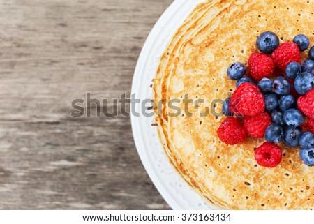 Fresh golden pancakes with raspberries, blueberries - stock photo