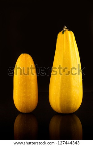 Fresh golden zucchini isolated on black with reflection