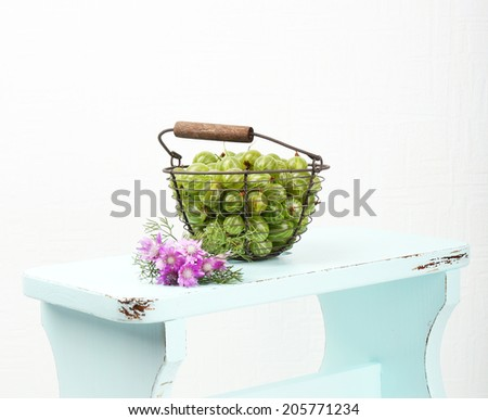 Fresh gooseberries in basket on white wall background - stock photo