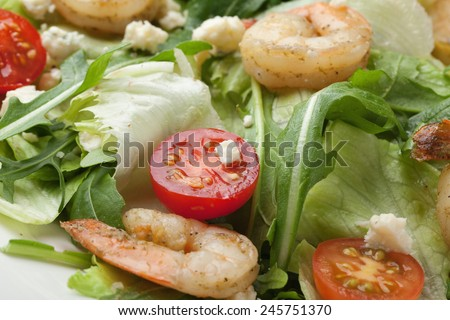 Fresh gourmet seafood salad with lettuce, rocket and corn greens, shrimps, cherry tomatoes, cheese  served in white plate - stock photo