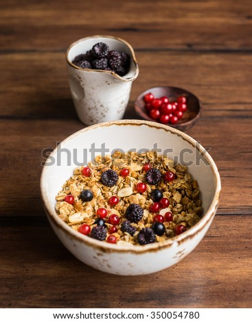 Fresh granola or muesli with toasted oat flakes, black and red currant, raspberry, blackberry, honeyed peanuts in a breakfast bowl on a wooden rustic kitchen table, selective focus - stock photo