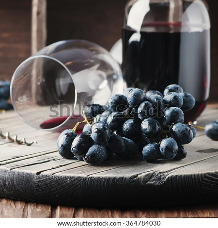 Fresh grape and red wine on the vintage table, selective focus and square image - stock photo