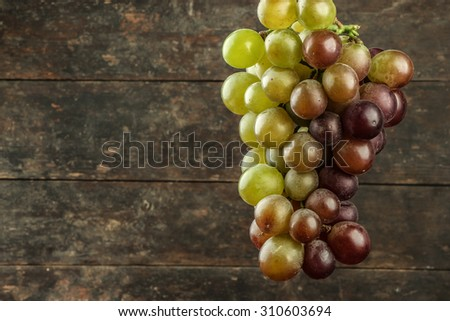Fresh grape is hanging with old wooden background.