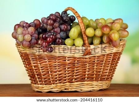Fresh grape on wicker mat on bright background - stock photo