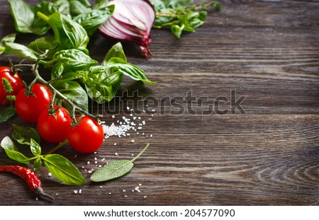 Fresh grape tomatoes with basil, spices and coarse salt on wooden board with copy space. - stock photo