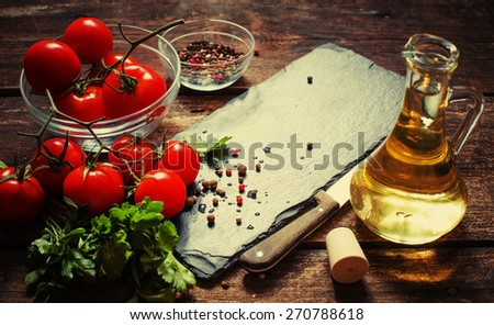 Fresh grape tomatoes with pepper for use as cooking ingredients on wooden background  - stock photo