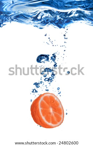Fresh grapefruit dropped into water with bubbles isolated on white - stock photo