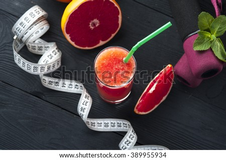 Fresh grapefruit juice, dumbbells and measuring tape on wooden table. Healthy food and fitness for weight loss. - stock photo