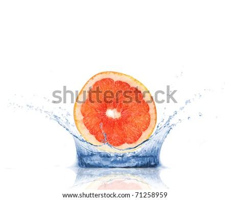 Fresh grapefruit slice dropped into water, isolated on white background - stock photo
