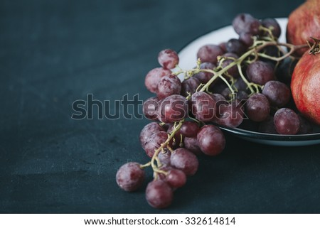 fresh grapes and pomegranate in old vintage plate, on dark blue colored table - stock photo