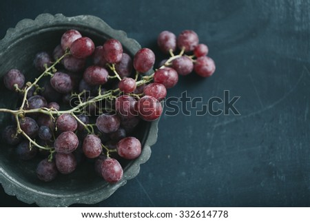 fresh grapes im old vintage plate, on dark blue colored table - stock photo