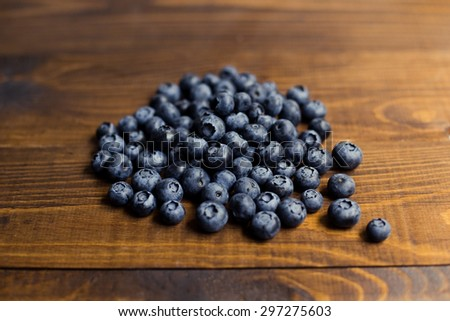 Fresh great bilberries or blueberries on wooden background. Selective focus