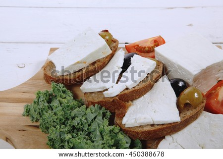 fresh greek feta cheese sandwich on wooden plate with hot green olives and black, goat cube, tomatoes kale over table - stock photo