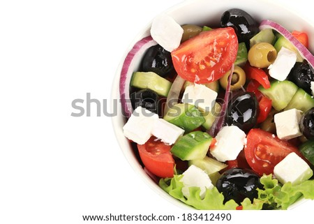 Fresh greek salad in clay bowl. Isolated on a white background.