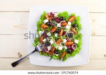 Fresh Greek salad on a plate - stock photo