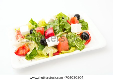 Fresh Greek salad on a plate on white background.