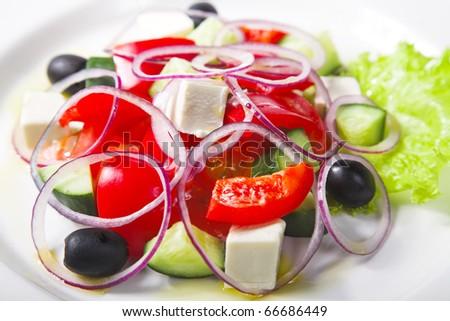 fresh Greek salad on white plate - stock photo