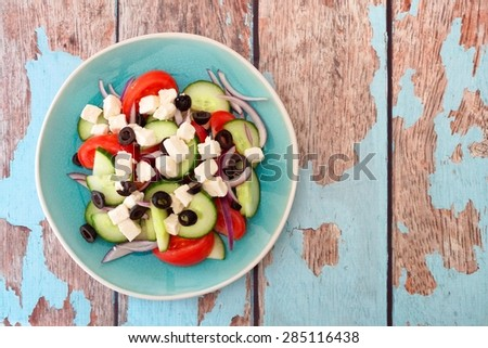 Fresh Greek Salad overhead view on a blue plate with rustic old wood background - stock photo