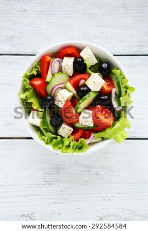 fresh greek salad top view in white bowl on boards - stock photo