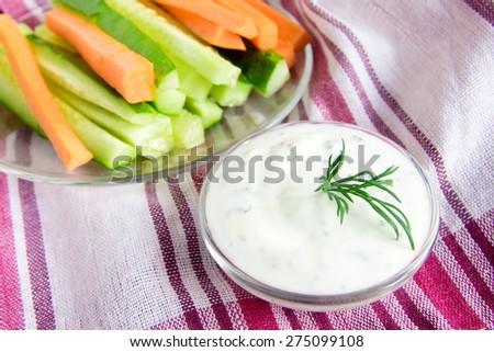 fresh Greek Tzatziki yogurt dip (sauce) and assorted vegetables on napkin - stock photo