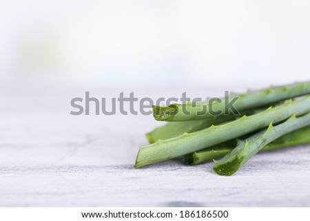 Fresh green aloe leaves on wooden table - stock photo
