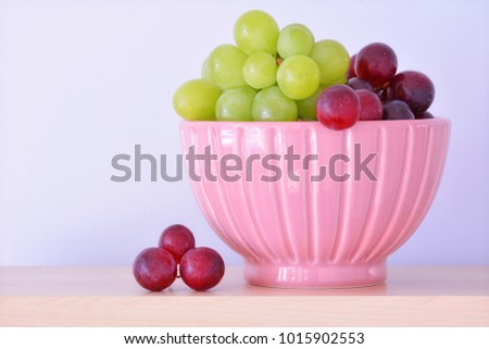 Fresh green and red grapes in pretty pink bowl in horizontal format with room for text