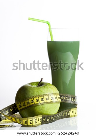 Fresh green apple juice with whole apple fruit and measuring tape isolated on white background. - stock photo