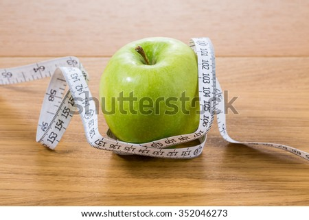 fresh green apple on a wooden table with measure close up