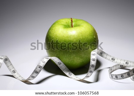 Fresh green apple with measure tape  over gray gradient - stock photo