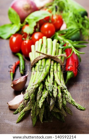 Fresh green asparagus bunch and vegetables on wooden board - stock photo