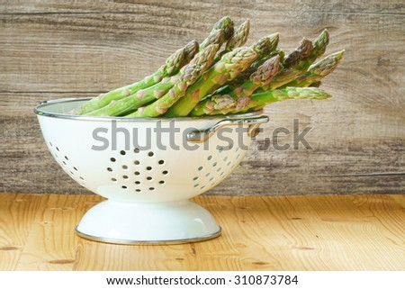 Fresh green asparagus in a white enamel colander on a rustic wooden table