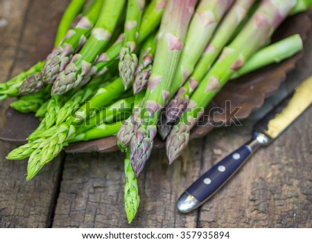 Fresh green asparagus on old wooden table. Shallow depth of field - stock photo