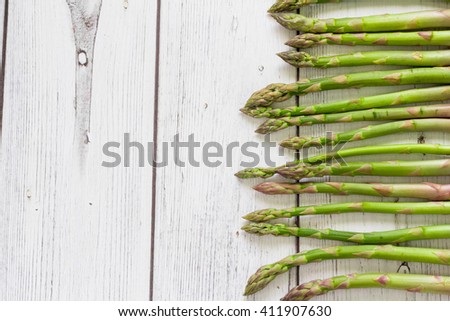 Fresh green asparagus on white wooden background - stock photo