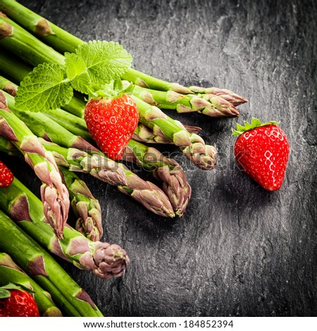 Fresh green asparagus spears and ripe colorful red strawberries garnished with a sprig of fresh peppermont on a dar textured background with vignetting and copyspace - stock photo