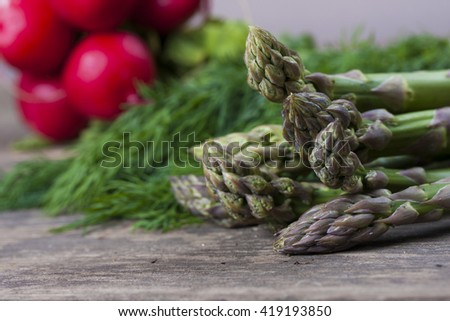 Fresh green asparagus spears, dill and radishes on old wooden table - stock photo