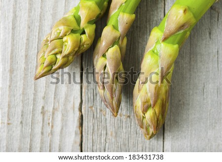 fresh green asparagus spears, old wood table background - stock photo