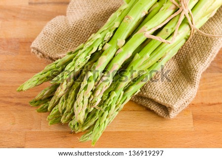fresh green asparagus sprouts in pouch   on wooden table
