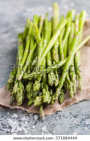 Fresh green asparagus with sea salt on a craft piece of paper and and on a marble table - stock photo