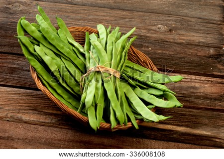 Fresh green beans in a basket on old wooden table. - stock photo