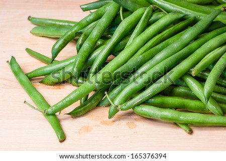 Fresh green beans on a wooden cutting board in kitchen