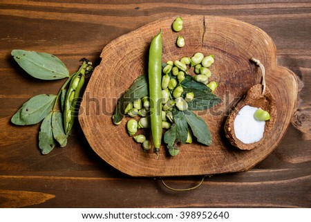 Fresh green beans seen from above on a rough wood floor brown color. Seasonings of Mediterranean cuisine: olive oil, salt. / Fresh Broad Beans - stock photo