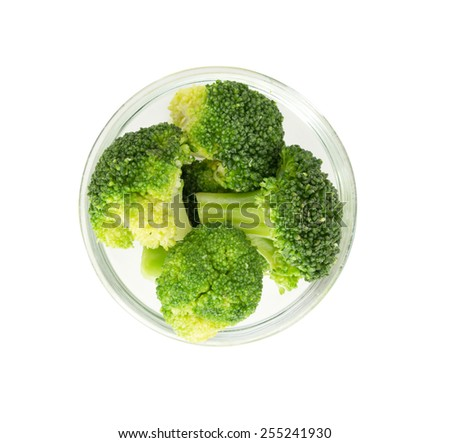 Fresh green broccoli in a glass bowl isolated on white. Top view. - stock photo