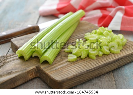 Fresh green celery stems on wooden cutting board closeup - stock photo