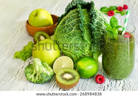 Fresh green detox smoothie on wooden background for healthy meal - stock photo