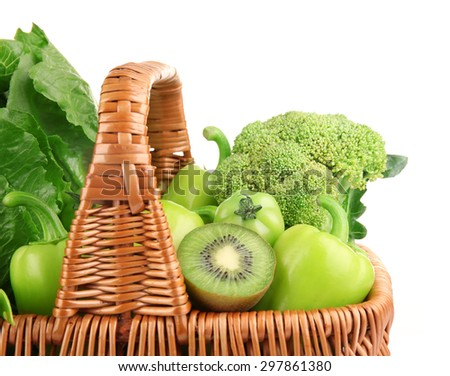 Fresh green food in wicker basket isolated on white - stock photo