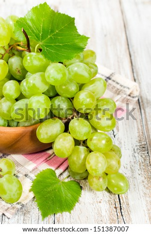 fresh green grapes in a wooden bowl, close-up
